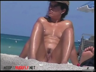 Amateur beach nudists stretching on the golden sand